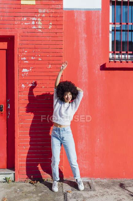 Женщина стоящая с поднятой рукой перед красным зданием — стоковое фото