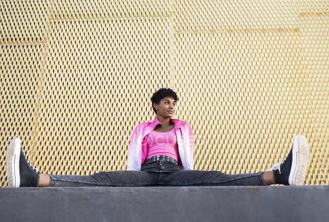 Молодая женщина смотрит в сторону, сидя, раздвигая ноги за стеной — стоковое фото