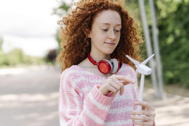 Рыжая женщина держит ветряк, стоя в парке — стоковое фото