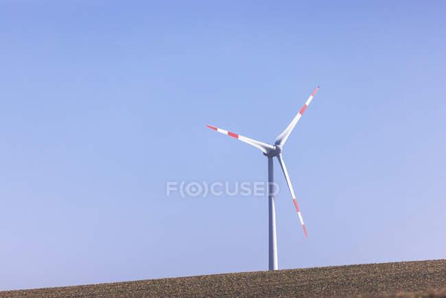 Ветряная турбина стоит на фоне ясного голубого неба — стоковое фото