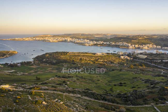 Мальта, Северный округ, залив Сент-Фелс, вид с воздуха на залив Мистра и прибрежный город в сумерках — стоковое фото