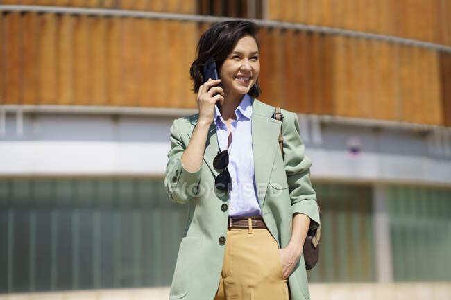 Улыбающаяся деловая женщина смотрит в сторону, разговаривая по смартфону — стоковое фото