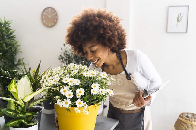 Улыбающаяся цветочница с цифровой таблеткой, пахнущей цветами в магазине — стоковое фото