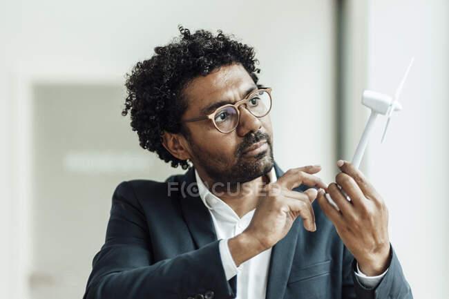 Мужчина-предприниматель с вьющимися волосами рассматривает модель ветряной турбины в офисе — стоковое фото