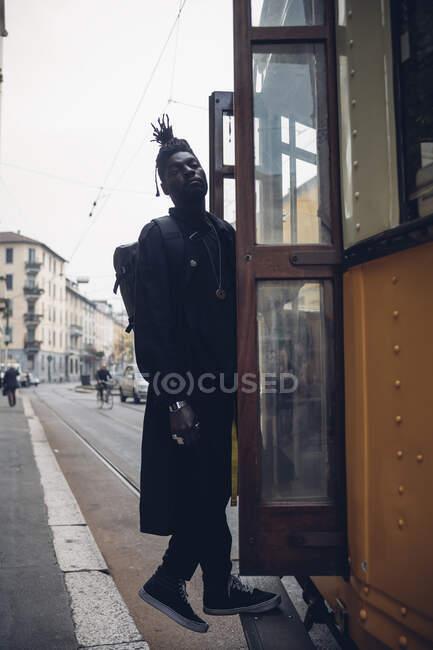 Jovem com mochila em pé na porta do bonde — Fotografia de Stock