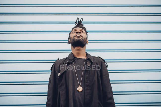Jovem olhando para cima, enquanto em pé na frente da parede corrugada azul — Fotografia de Stock
