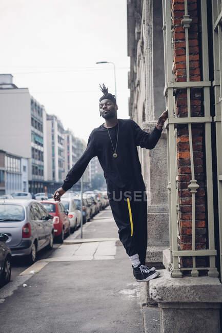 Jovem inclinado na parede da cidade — Fotografia de Stock