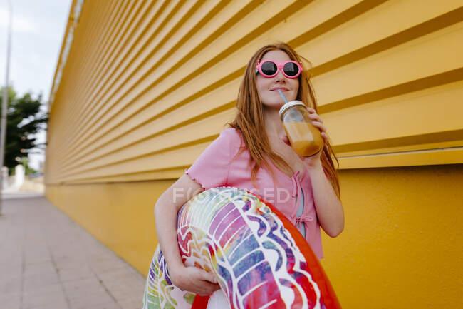 Жінка в сонцезахисних окулярах тримає надувне кільце, коли п