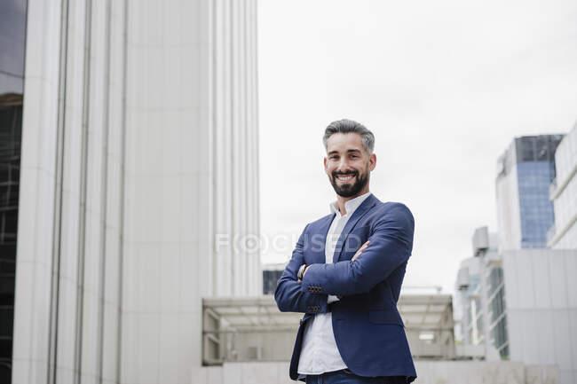 Уверенный мужчина-предприниматель улыбается, стоя со скрещенными руками — стоковое фото