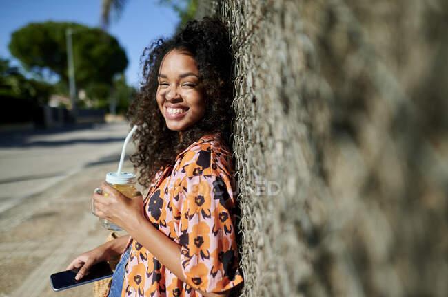 Щаслива жінка з лимонадом і розумним телефоном у сонячний день. — стокове фото