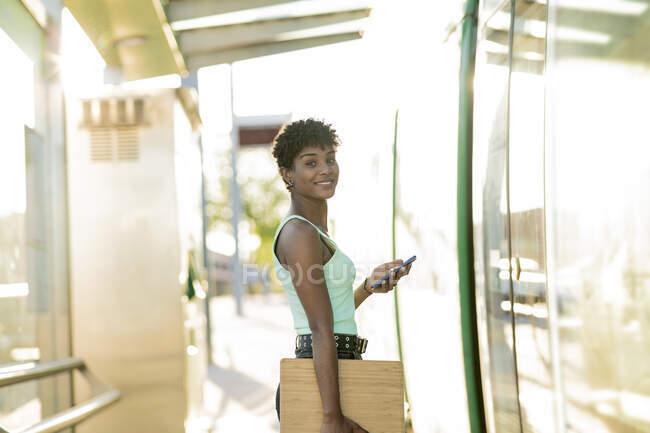 Молодая женщина, стоящая у входа в трамвай с беспроводными технологиями — стоковое фото