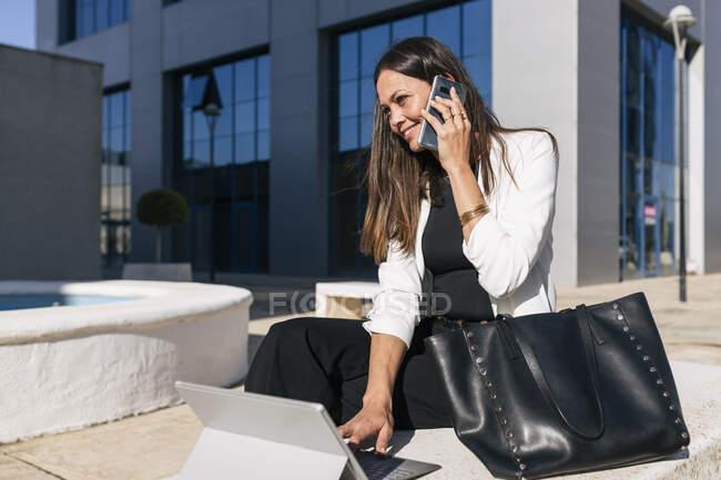 Зрелая предпринимательница с цифровым планшетом, улыбающаяся во время разговора по мобильному телефону — стоковое фото