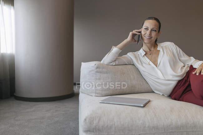Улыбающаяся предпринимательница разговаривает по смартфону и смотрит в сторону, сидя на диване — стоковое фото