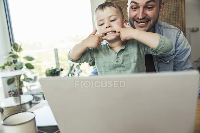 Ragazzo prendere in giro mentre seduto con il padre facendo videochiamata attraverso il computer portatile a casa — Foto stock
