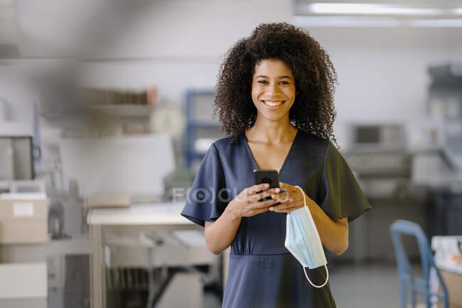 Улыбающаяся деловая женщина с мобильным телефоном и защитной маской на лице стоит в офисе — стоковое фото