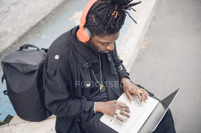 Jovem trabalhador freelance com fones de ouvido usando laptop enquanto está sentado no caminho — Fotografia de Stock