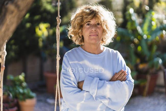 Зрелая женщина стоит со скрещенными руками на заднем дворе — стоковое фото
