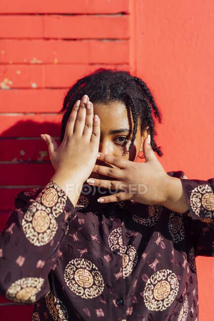 Jovem mulher olhando enquanto cobre o rosto na frente da parede vermelha — Fotografia de Stock