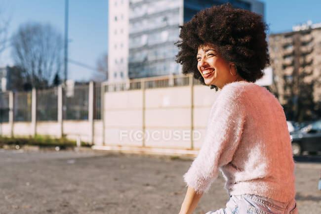 Веселая женщина с афро-волосами смотрит в сторону в солнечный день — стоковое фото