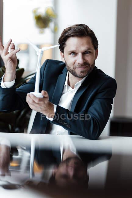 Улыбающийся бизнесмен жестикулирует, держа в офисе модель ветряной турбины — стоковое фото