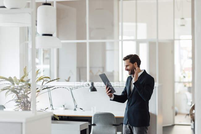 Sonriente hombre de negocios saludando de la mano a la videollamada a través de tableta digital en la oficina - foto de stock