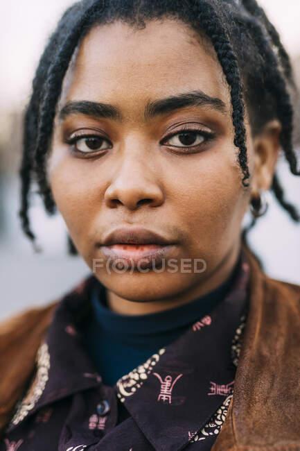 Jovem mulher com locos penteado olhando — Fotografia de Stock