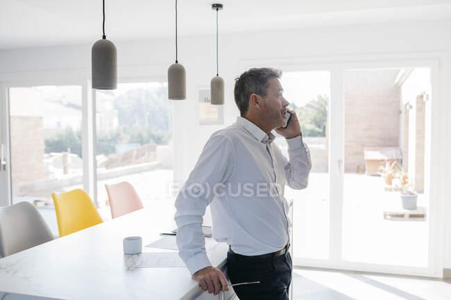 Бизнесмен смотрит в сторону, разговаривая по смартфону в домашней кухне дома — стоковое фото