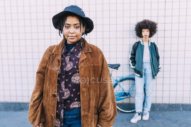 Mulher vestindo chapéu e sobretudo de pé com amigo no fundo — Fotografia de Stock