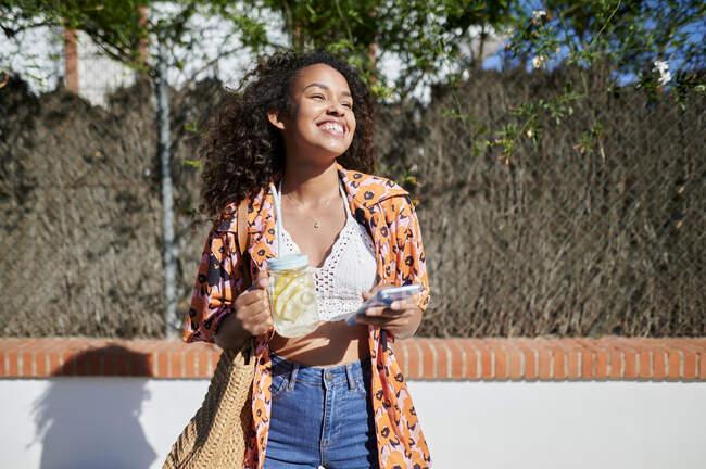 У сонячний день молода жінка з лимонадом і мобільним телефоном. — стокове фото