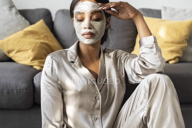 Серьёзная женщина в маске для лица сидит дома в гостиной — стоковое фото