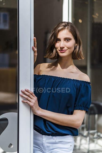 Посмішка жінка-підприємець з середньою довжиною волосся стоячи біля дверей — стокове фото