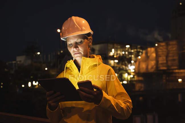 Женщина-профессионал в жёлтой каске и плаще с использованием беспроводных технологий ночью — стоковое фото