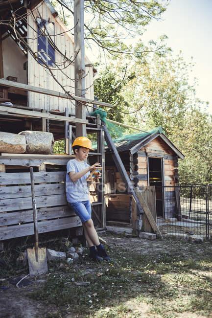 Мальчик в жёлтой каске рассчитывает на игрушке, опираясь на кроличью берлогу на заднем дворе — стоковое фото