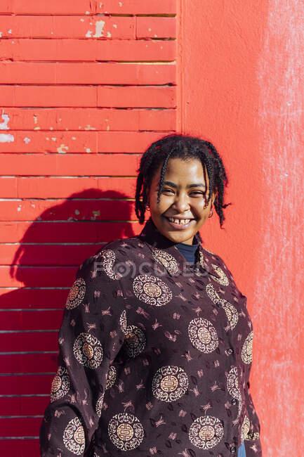 Mulher sorrindo em pé na frente da parede vermelha — Fotografia de Stock