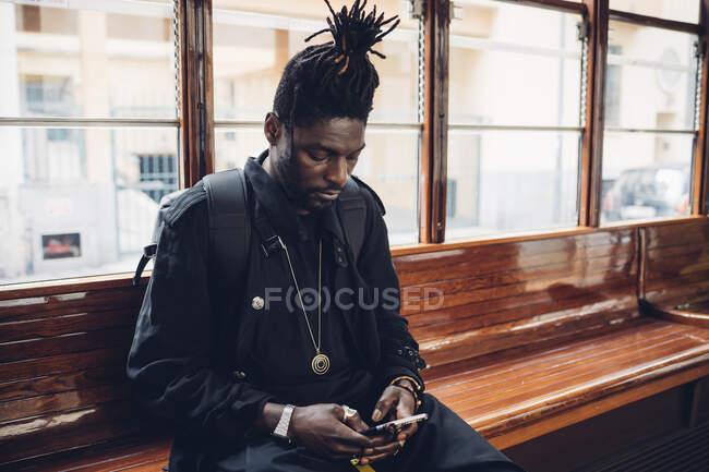Jovem com locos penteado usando telefone celular sentado em bonde — Fotografia de Stock