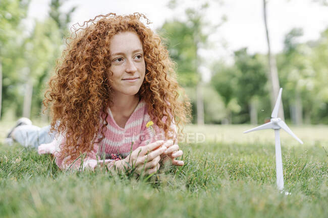 Молодая рыжая женщина, лежащая в парке, отворачиваясь — стоковое фото