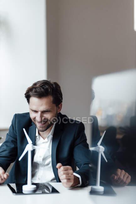 Улыбающийся предприниматель смотрит на модель ветряной турбины в офисе — стоковое фото