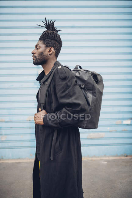 Homem elegante de pé com mochila por parede ondulada azul — Fotografia de Stock