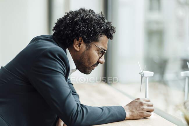 Мужской профессиональный опираясь на стол во время изучения модели ветряной турбины в офисе — стоковое фото