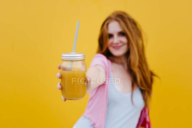 Жінка показує напій, стоячи перед стіною. — стокове фото