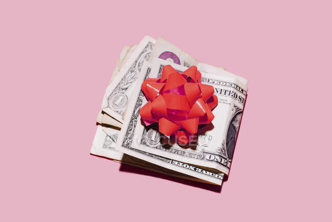 Estudio de tiro de billetes de dólar doblados con lazo de regalo rojo - foto de stock