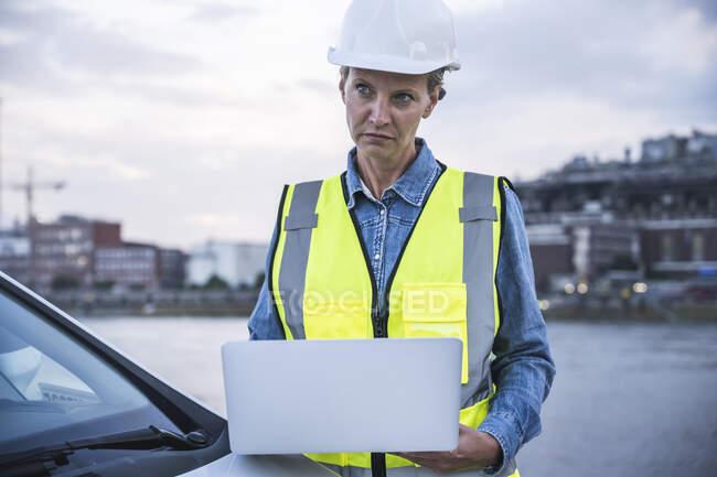 Задумчивая женщина-профессионал держит ноутбук в машине — стоковое фото
