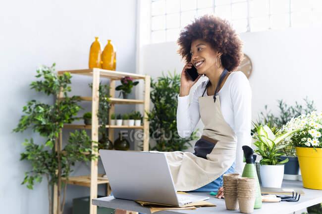 Женщина-флорист разговаривает по мобильному телефону, сидя за ноутбуком на столе — стоковое фото