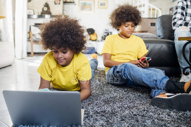 Братья-близнецы используют беспроводные технологии дома — стоковое фото