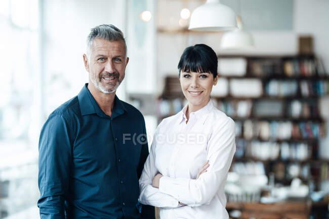 Уверенные владельцы мужского и женского пола стоят вместе в кафе — стоковое фото