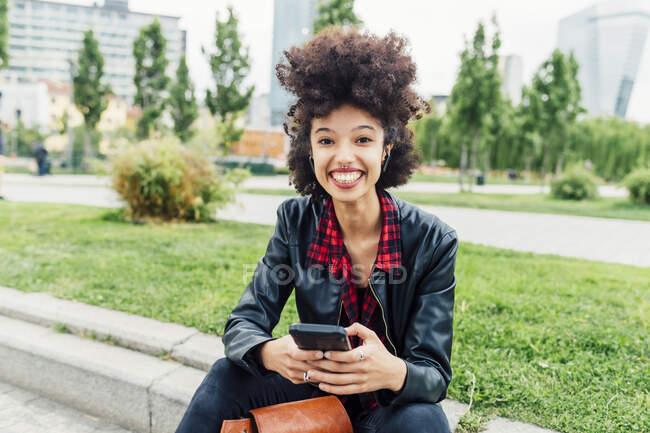 Улыбающаяся женщина сидит с мобильным телефоном в парке — стоковое фото