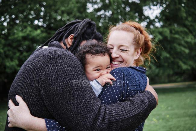 Família feliz abraçando filho no parque — Fotografia de Stock