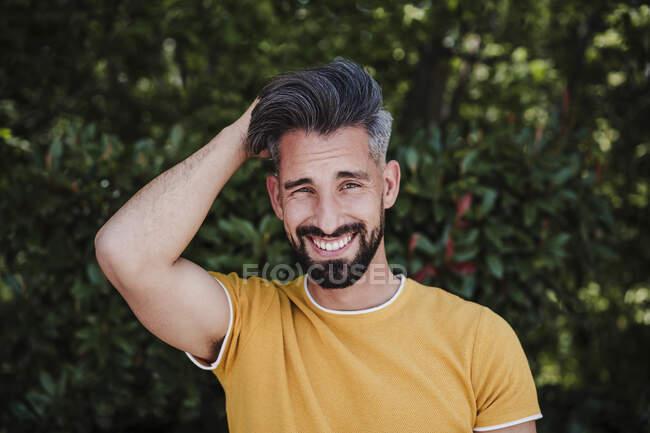 Улыбающийся бородатый мужчина с рукой в волосах в парке — стоковое фото
