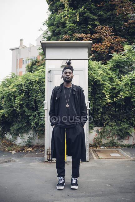 Homem na moda de pé com as mãos em bolsos na estrada — Fotografia de Stock