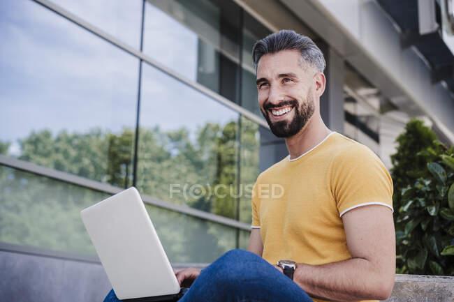 Улыбающийся бизнесмен смотрит в сторону, сидя с ноутбуком — стоковое фото